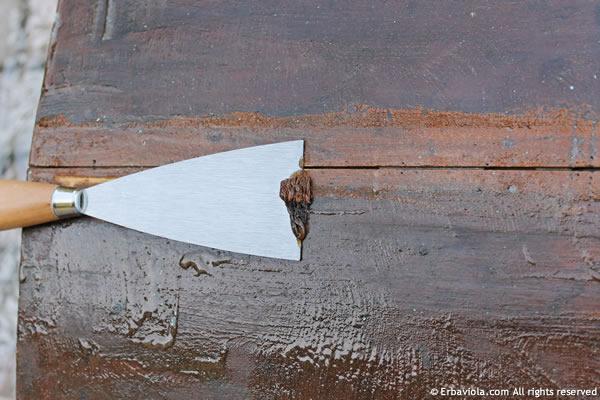 raschiamento della vecchia vernice con la spatola