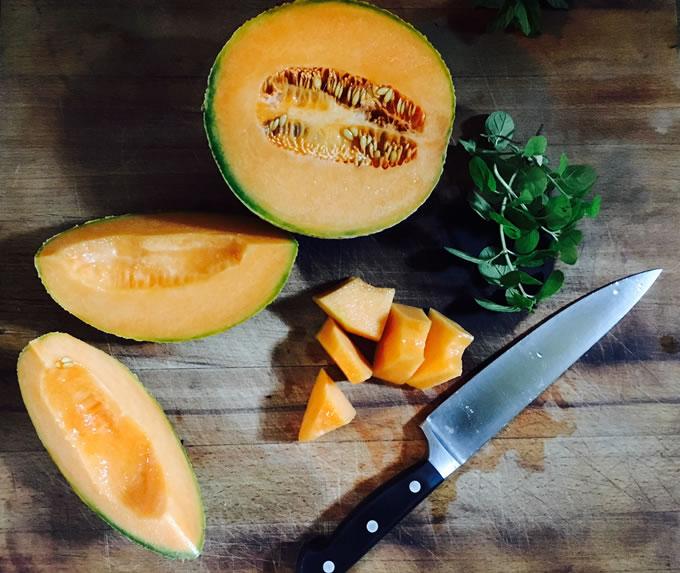 melone tagliato e intero sul tagliere