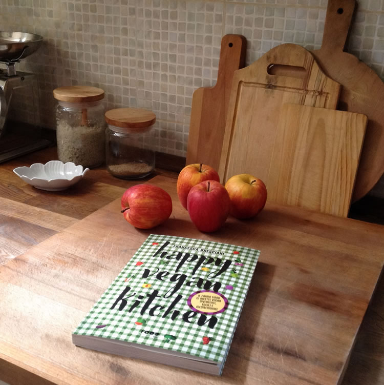 happy vegan kitchen sul piano di lavoro con 4 mele